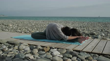 sobre : Athletic girl is making physical exercises on seashore. She is sitting on floor stretching leg and leaning to it