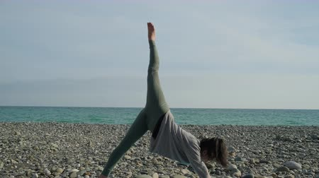 tutmak : Young athletic girl is practicing yoga in morning time on sea shore. She is standing on legs and hand on floor and stretching one leg up Stok Video
