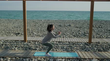 tartás : Sporty girl is squatting standing on pebble beach in daytime. She is training, keeping sporty shape of body