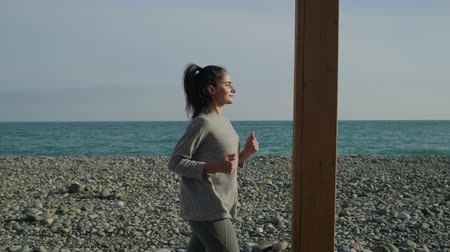 keep fit : Pretty brunette woman is jogging in sunny day alone over seashore. She is training alone to keep fit, healthy activities Stock Footage
