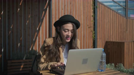 veranda : Pretty brunette girl is browsing in internet by notebook in open veranda. She is smiling looking on display and resting in sunny day