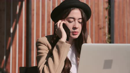 veranda : Brunette woman is calling by cell phone and working with notebook in open veranda in sunny day. She is explaining to her interlocutor emotionally, close-up of face
