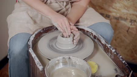 varázsló : Female artist is shaping a cup from clay piece on potter wheel