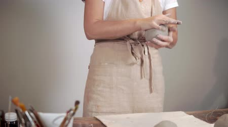 mashing : Female master is kneading clay in working studio, standing near table