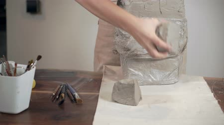 hrnčíř : Female sculptor is putting on table three pieces of gray clay, close-up view