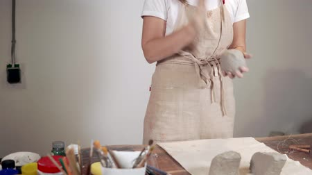 feiticeiro : Woman sculptor is shaping round blanks from gray clay in workshop Stock Footage