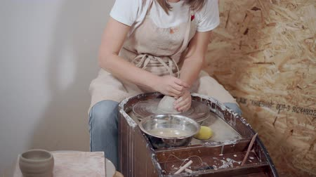 oleiro : Woman is kneading clay on potters wheel in workshop