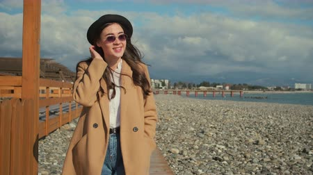 regozijo : Pretty woman is strolling on empty seashore in spring time. She is smiling and rejoicing, holding hands inside pockets of coat Stock Footage