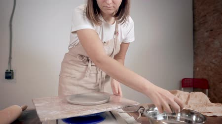 afstemmen : Female master is shaping edges of ceramic plate, rotating it on spinning stand
