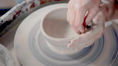 büyücü : Woman is wetting and softening clay on potters wheel in pottery, close-up Stok Video