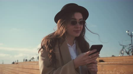 walk behind : Cheerful young lady is reading messages in mobile phone outdoors. She is looking on screen and smiling, portrait in background of sky and walking passers Stock Footage