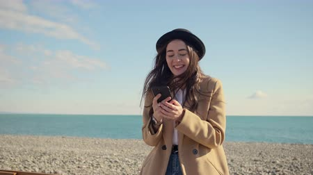 news stand : Brunette smiling woman is sending sms by cell phone and having fun in seashore in sunny day. She is standing alone in springtime, beautiful horizon in background