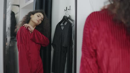 tentar : Charming brunnete girl posing in a new long red dress in a dressing room. Woman tries on new stylish clothes. Shopping in a mall. Posing in front of a mirror.