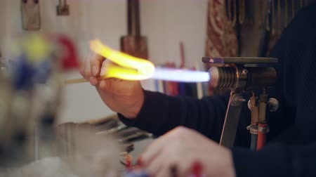 glass master : Gaffer is preparing glass stick for glassblowing, warming it in flame of torch,