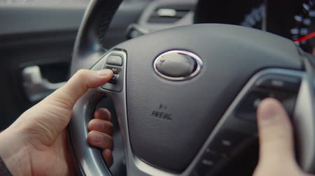 bérlet : Close-up shot of male driver using audio display shortcuts on a steering wheel to turn volume up and down. Modern car with remote audio system control.