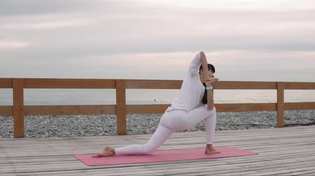 duše : Flexible woman in a white sportswear standing in yoga warrior pose I. Meditating, stretching and strenthening her body and soul outdoor by the beach. Dostupné videozáznamy