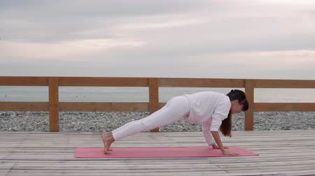 meditující : Side view shooting of a woman practicing yoga outdoor on wooden terrace on a pink mat. Woman in a upward facing dog pose. Challenging her body.