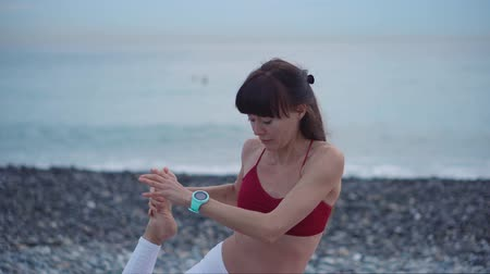 герой : Charming brunette woman in sportswear in a yoga pose. Flexible woman stretching by the sea, outdoor sport activity on the shore. Стоковые видеозаписи
