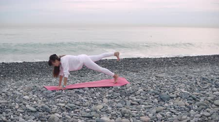 planking : Side view shooting of a core body workout on a beach shore in the morning, one-legged plank on yoga mat. Yoga practice by the ocean. Core Strenght. Stock Footage