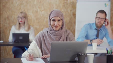 İslamiyet : Beautiful muslim woman in hijab sitting at the table in office and working. Charming islamic woman looking in camera. Colleagues on the background. Stok Video