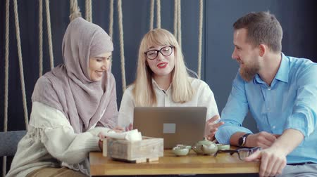 élénk : Muslim woman in hijab with her caucasian friends sitting at cafe table with laptop and having lively conversation. Friends laughing together in free time. Carefree lifestyle.