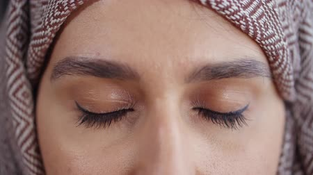 eyes closed : Close-up shot of a muslim woman in hijab with closed eyes, lovely chocolate skin. Beautiful deep hazel eyes. Stock Footage