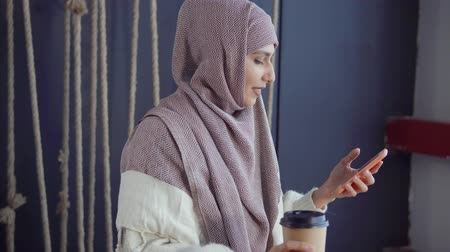 foulard : Side view portrait of an attractive middle-east woman in hijab laughing at sms text message on smartphone with a cup of coffee in other hand. Texting with friends. Filmati Stock