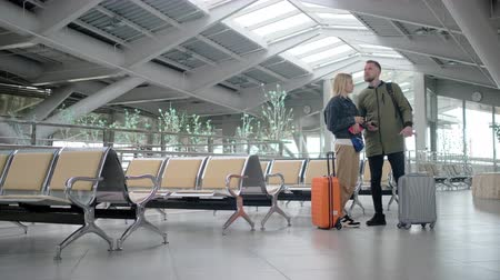 chegar : Married couple with suitcases are inside waiting hall of station in daytime