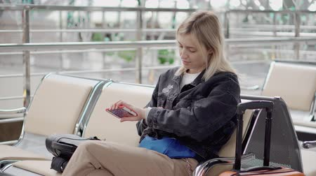 salone : Blonde woman is using smartphone in waiting area in airport or railway station