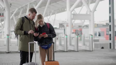 entrance : Two passengers are using smartphones, standing on platform of railway station Stock Footage