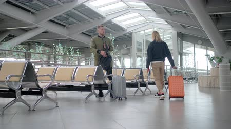 their : Man and woman are walking through departure lounge with suitcases and sitting