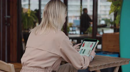 catalogo : L'ospite femminile del caffè è seduta all'aperto e fa shopping online per tablet Filmati Stock