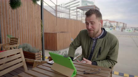 interactive table : Young man is communicating by internet call through tablet sitting outdoors