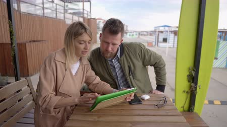 haver : Man and woman are looking at display of tablet in outdoor cafe