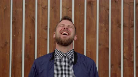 Portrait of laughing young man standing outdoors, medium shot Stok Video