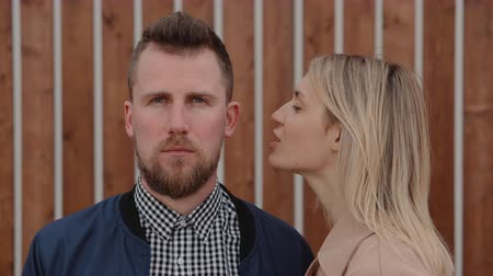 Pretty blonde woman is whispering on ear of handsome bearded man outdoors