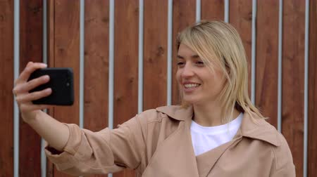 Blonde woman is talking by video call on her smartphone outdoors