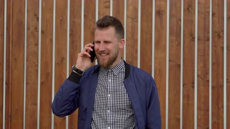 Handsome man is talking by mobile phone emotionally, standing outdoors