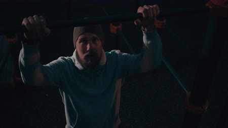 Bearded man is is making pull-up on bar of sportive area in night