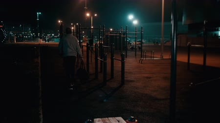 Young man is going out from sports ground in park at night Stok Video