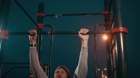 Athletic man is training on horizontal bar in cold night time, work out Stok Video