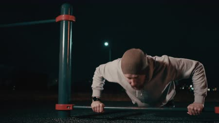 Man is doing push-ups outdoors in sports area in night time