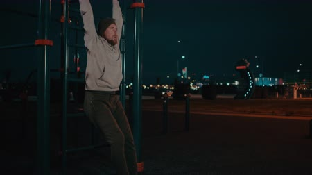 Bearded guy is hanging on training area in park in night and lifting legs Stok Video