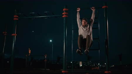 Sportive man is lifting legs hanging on horizontal bar outdoors in night Stok Video