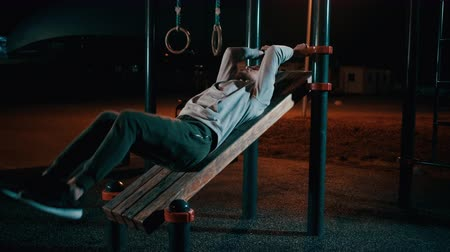Man is lying on outdoor sport equipment in park and training legs and abdomen