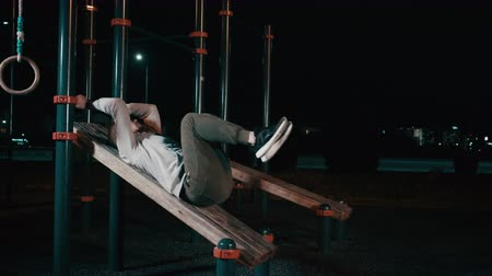 Young sporty man is lifting legs lying on sports equipment in night park