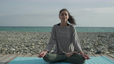 Young girl relaxing on a beach meditating.