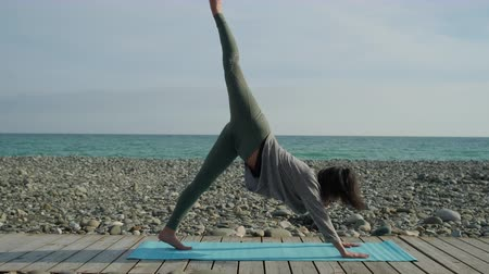 Girl practicing yoga on beach shore alone. Stok Video