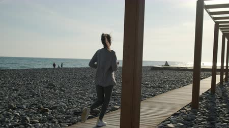 Fitness woman running in the evening on beach. 무비클립