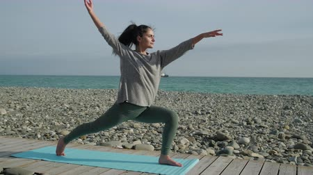 Woman doing yoga on sea shore. Stok Video